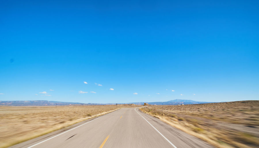 Sky Road Direction Transportation The Way Forward Landscape Blue Desert Environment Diminishing Perspective Land Nature Scenics - Nature Day Tranquil Scene Copy Space Non-urban Scene Clear Sky Sign No People Outdoors Arid Climate Climate Dividing Line