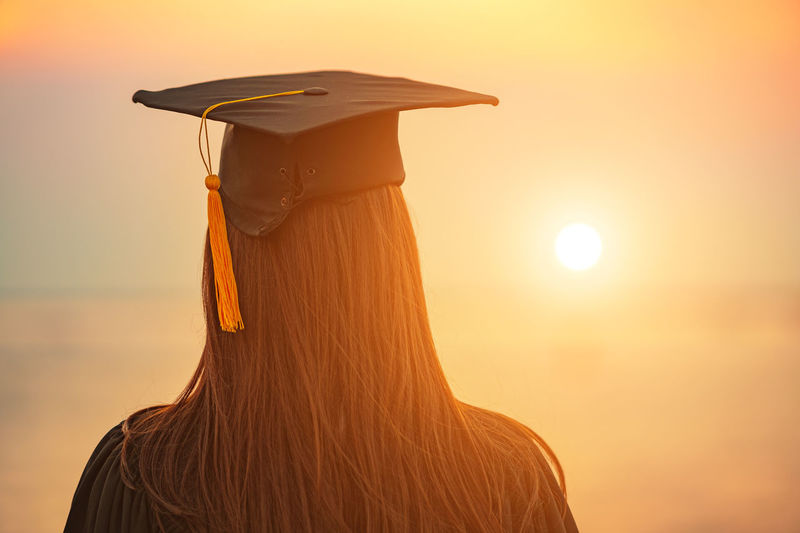 Rear view of woman wearing mortarboard while standing against orange sky