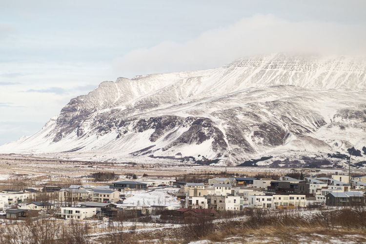 Aerial view of townscape by snowcapped mountain against sky