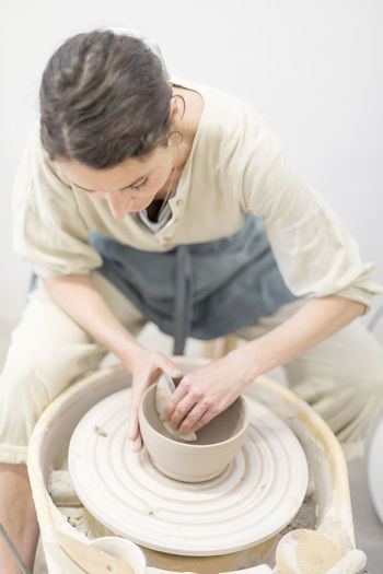 Young female sitting by table and making clay or ceramic mug in her working studio Art And Craft Ceramist Craft Creativity Expertise Holding Indoors  Making Molding A Shape Occupation One Person Pottery Preparation  Real People Shape Skill  Spinning Three Quarter Length Working Workshop