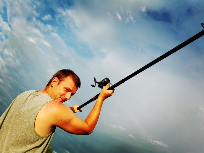 Mid adult man holding fishing rod against sky