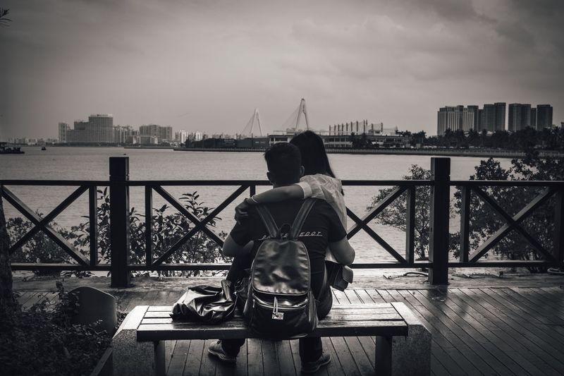Rear view of men sitting on bridge over river against sky