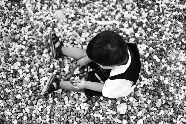 High angle view of boy sitting on pebbles