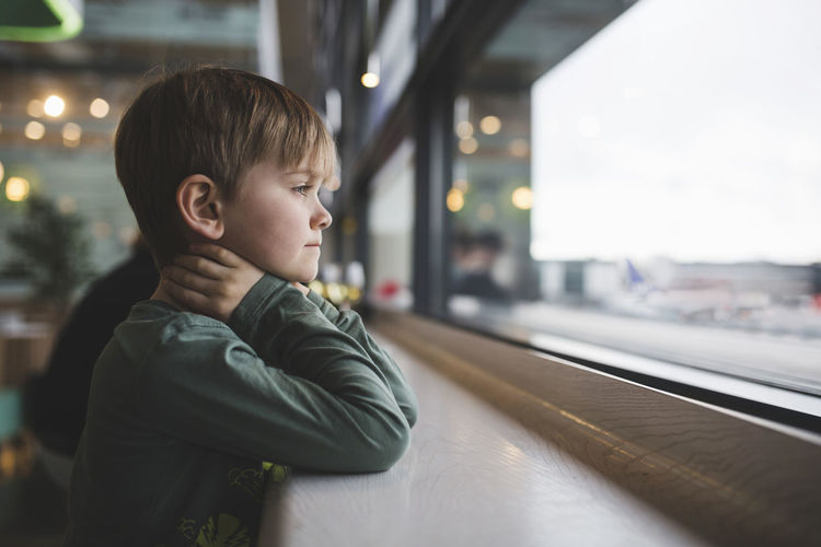Thoughtful boy leaning on table by window of restaurant