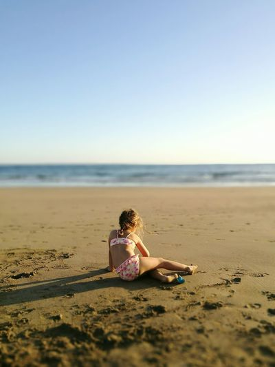 Full length of girl sitting on beach against sky