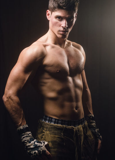 Portrait of muscular young man against black background
