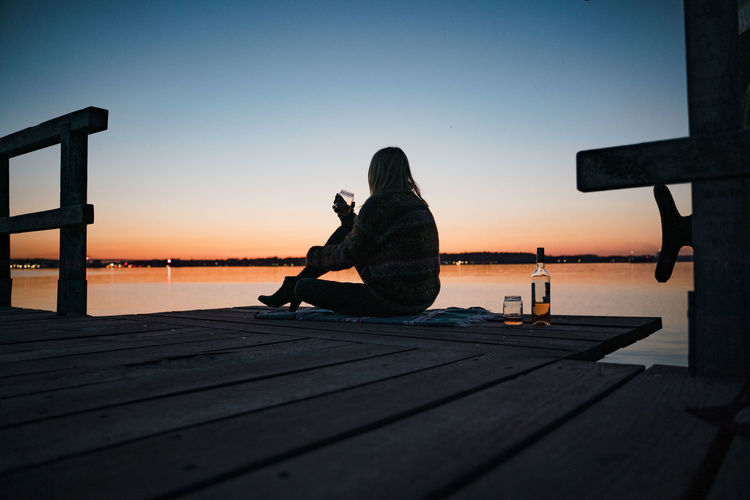 Woman sitting on pier over sea against clear sky during sunset
