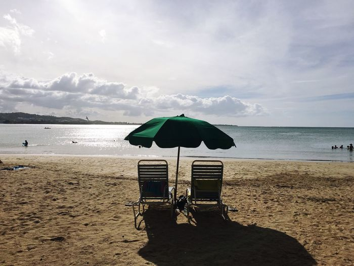 Lounge Chairs And Umbrella At Beach Against Sky On Sunny Day