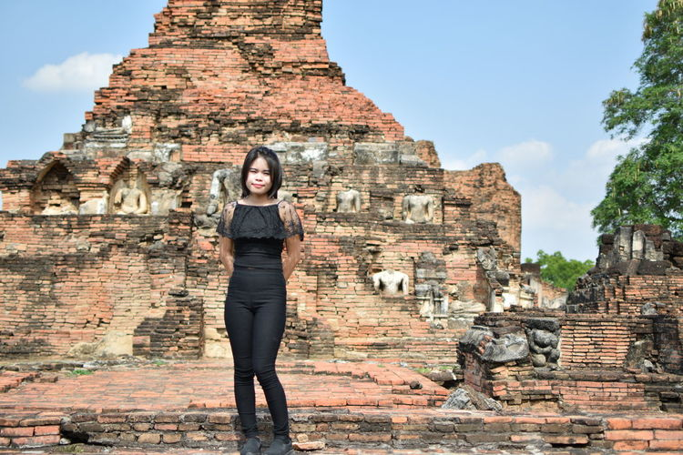 Portrait of young woman standing by old ruin temple against blue sky during sunny day