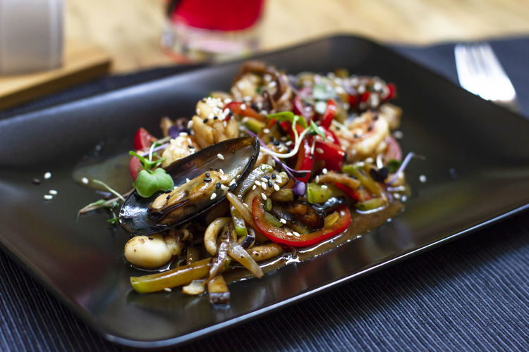 Salad with seafood mussels, octopus and vegetables in black plate on the table