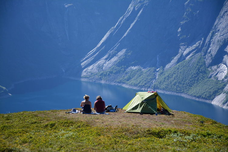 People Sitting By Tent On Mountain Peak Against Lake