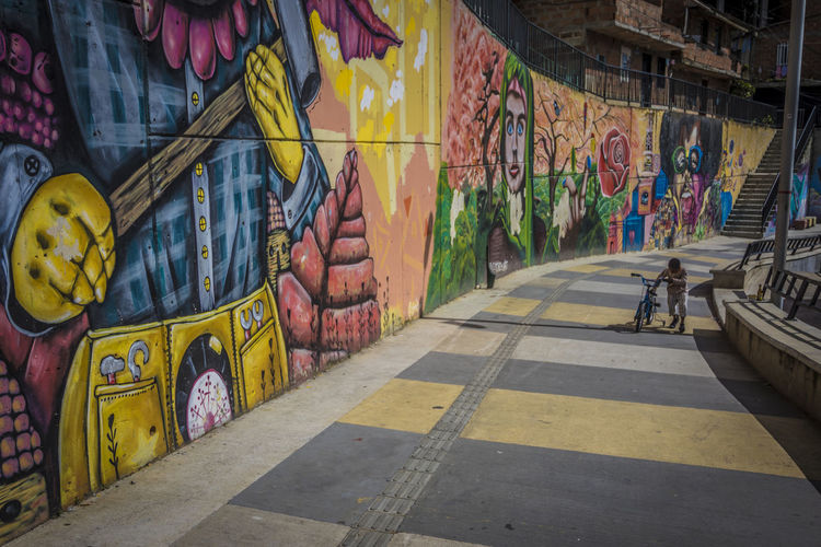 Architecture Art And Craft Built Structure City Comuna 13 Creativity Day Direction Empty Graffiti Multi Colored Mural No People Outdoors Paint Road Street Street Art The Way Forward Transportation Wall Wall - Building Feature