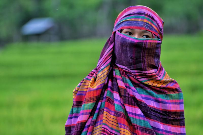 Woman wearing burka looking away while standing outdoors
