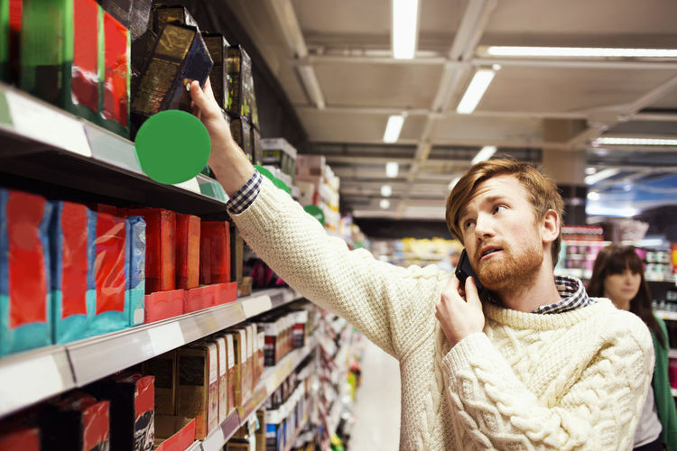 Full length of man looking at mobile phone in store