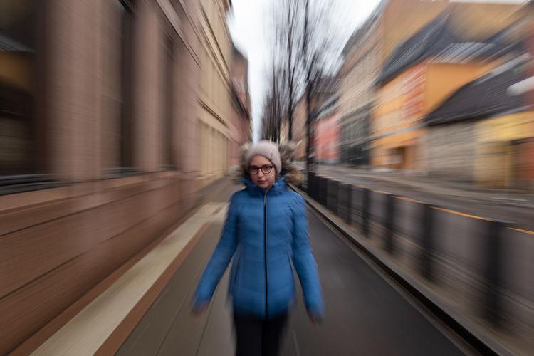 Portrait of girl standing on sidewalk in city
