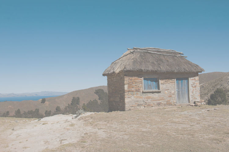Hiking at Isla del Sol Ancient Civilization Ancient History Blue Building Exterior Clear Sky Day Hill History Hut Little House No People Outdoors Scenic Landscapes Scenic View Thatched Roof Travel Destinations
