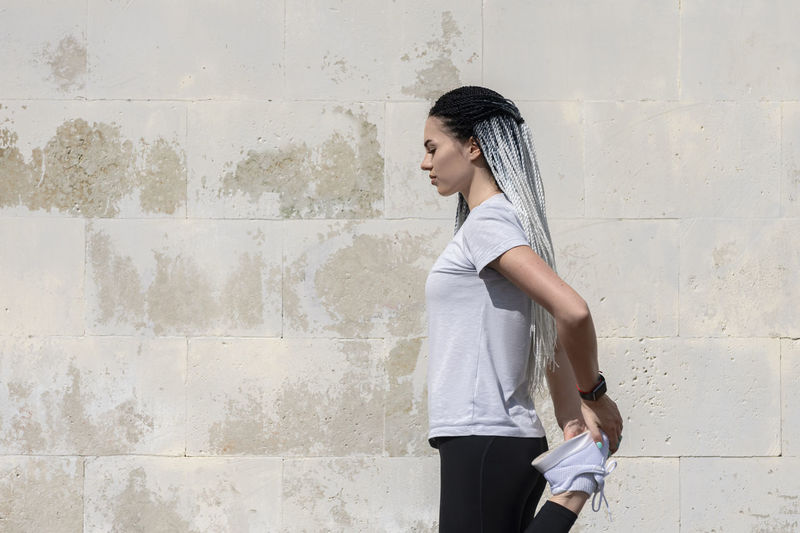 Side view of young woman standing against white wall