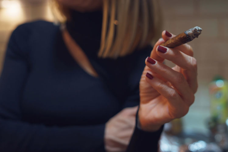 Midsection of woman holding cigar