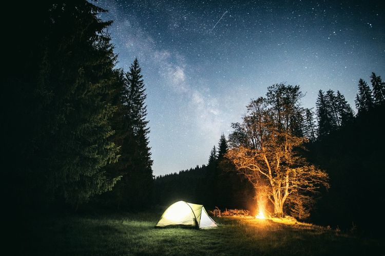 Illuminated tent by campfire on grassy field against star field at night