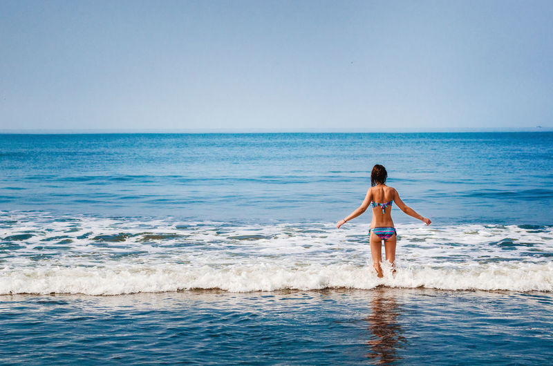 Girl standing in the ocean and looking at the horizon Beauty In Nature Bikini Enjoyment Girl Goa Horizon Over Water Idyllic India Lifestyles Nature People Of The Oceans Sea Seascape Shore Swimming Tranquil Scene Vacations Watching Water Wave Woman Feel The Journey People And Places International Women's Day 2019