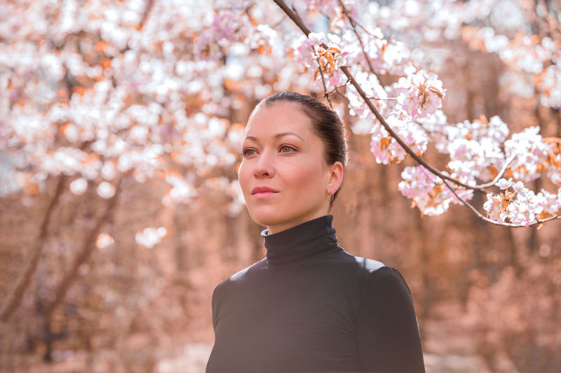 Portrait of young woman standing by cherry blossom tree