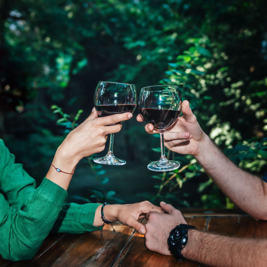 Couple Toasting With Red Wine On A Date Romantic Dinner Couple Red Wine Toasting Toasting Glasses Date Relationship Dating Restaurant Happiness Romance Anniversary Green Alcohol Two People Young Dinner Lunch Wineglass Celebratory Toast Glass Holding Celebration Togetherness Holding Hands