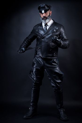 Full length of man wearing costume against black background
