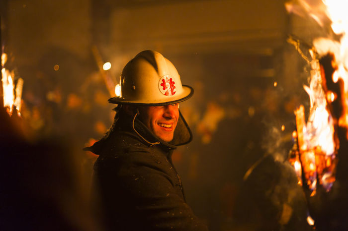 Chienbaese festival. Switzerland, Liestal, Rathausstrasse 25, 18th of February 2018. Close-up of a festival participant carrying burning broom shaped wooden logs through the old town. Brave Burning Firefighter Flames Hot Tradition Adult Arts Culture And Entertainment Burning Culture Festival Fire Hat Heat - Temperature Helmet Liestal One Person Parade Real People Side View Standing Swiss Switzerland Waist Up Wood - Material