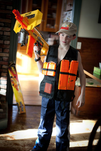 Locked and loaded for nerf gun war with older brothers, he has the advantage. Boys Life Boys Toys Business Casual Clothing Childhood Depth Of Field Fashion Front View Holding Indoors  Large Group Of Objects Leisure Activity Lifestyles Looking Men Music Nerf Gun Occupation Ready For Battle Real People Selective Focus Standing Women