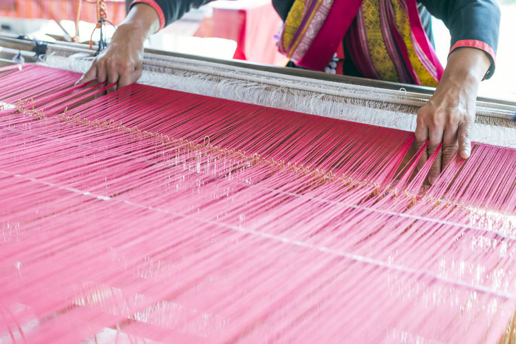 Close-up of female weaving cotton