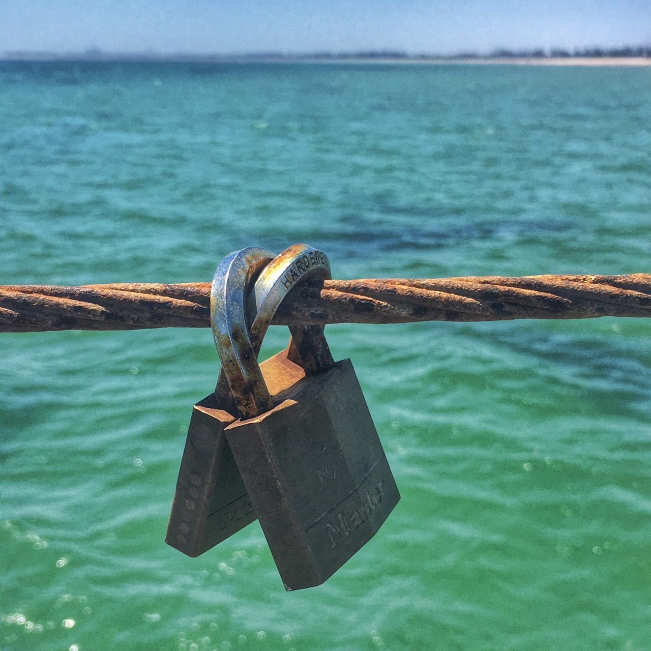 padlock, security, lock, water, metal, safety, love lock, sea, protection, hanging, chain, no people, outdoors, hope, love, day, close-up, horizon over water, sky