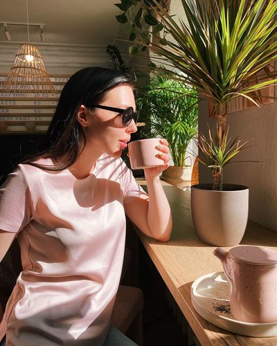 Young woman drinking coffee while sitting at cafe