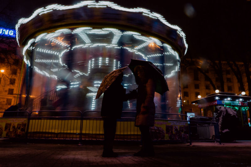 Night Blurred Motion Illuminated Motion Arts Culture And Entertainment Amusement Park Amusement Park Ride Real People City Leisure Activity Incidental People People Full Length Carousel Street Architecture Speed Men Adult Outdoors