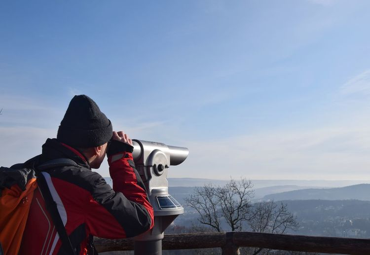 Man Looking Through Coin-Operated Binoculars Against Sky During Winter