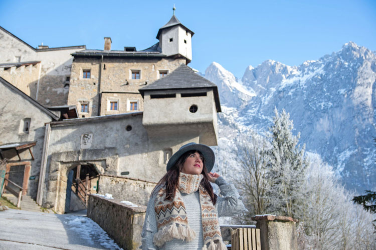 Woman in winter clothes in front of an medieval castle.