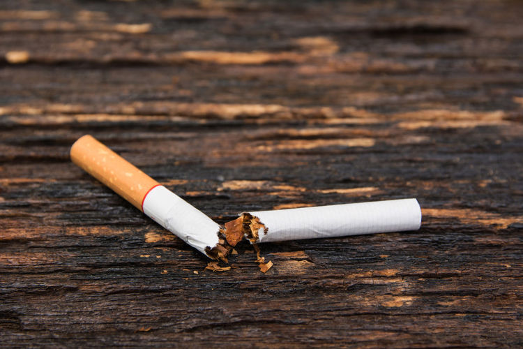Close-Up Of Broken Cigarette On Wooden Table