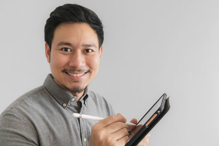 Portrait of smiling man holding smart phone against white background