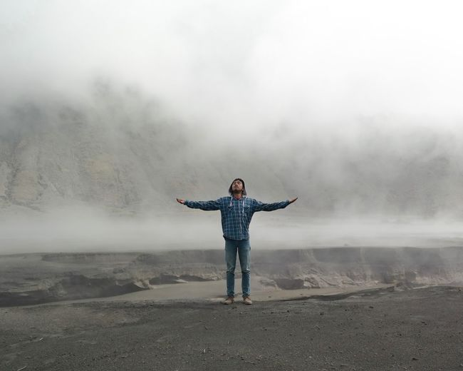 Full length of man with arms outstretched standing on cliff during foggy weather