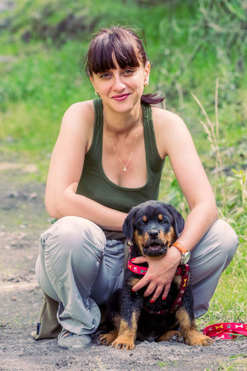 Full Length Portrait Of Woman Crouching With Rottweiler Puppy On Footpath