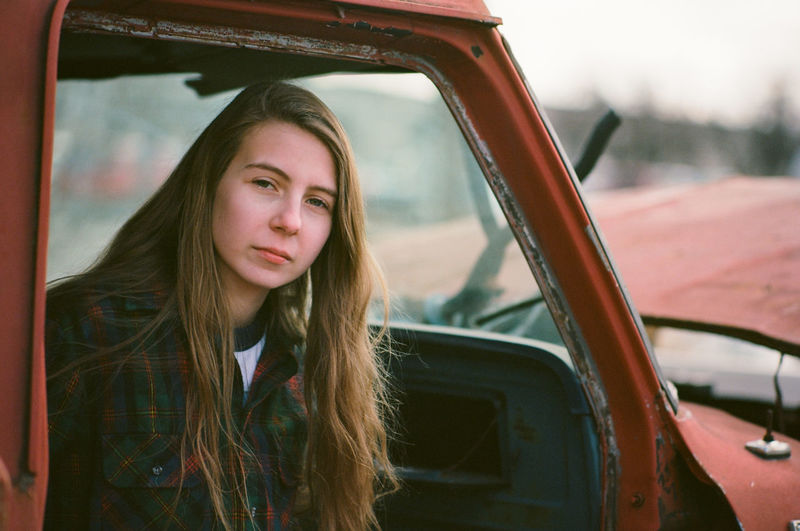 Portrait of young woman sitting in abandoned car