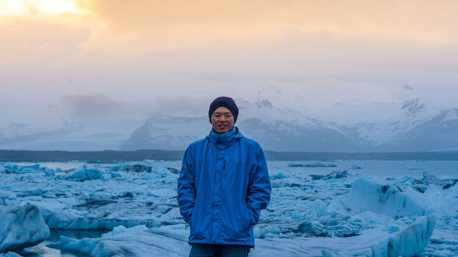 Portrait of man standing by frozen sea during sunset