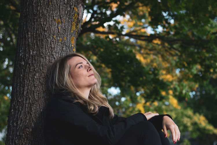Young woman sitting on tree trunk