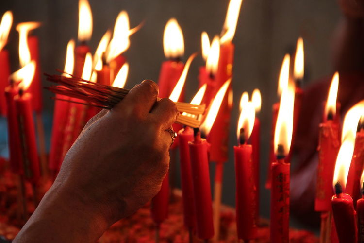 Cropped Hand Lighting Incenses On Lit Candle At Temple