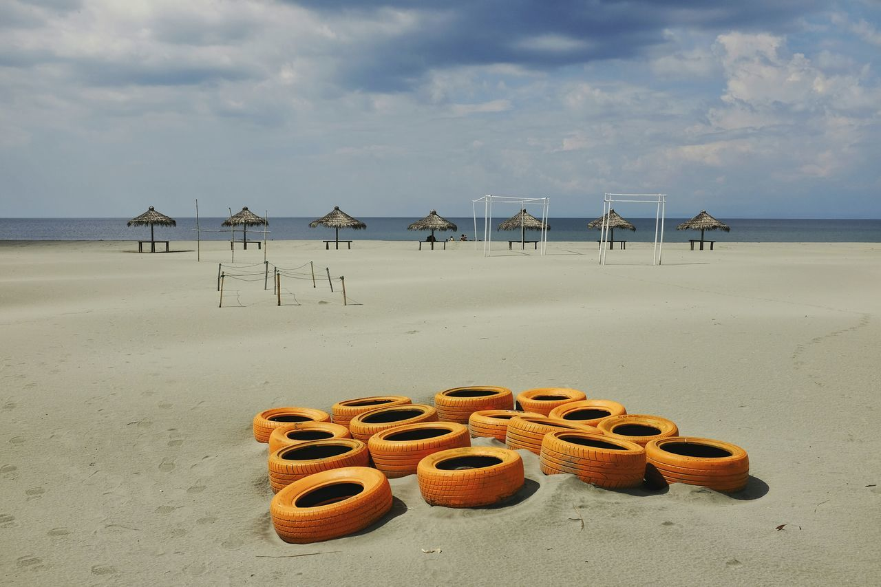 High angle view of yellow tires on sand at beach against cloudy sky