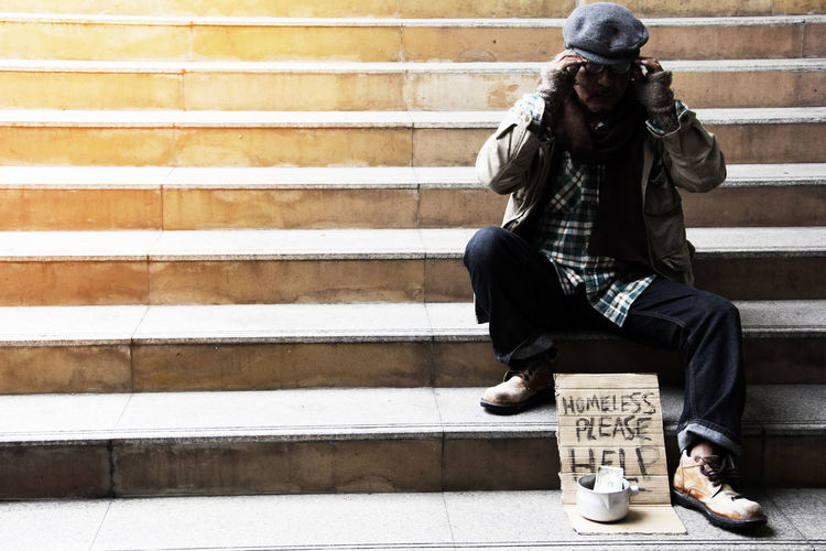 Full length of beggar with message sitting on steps