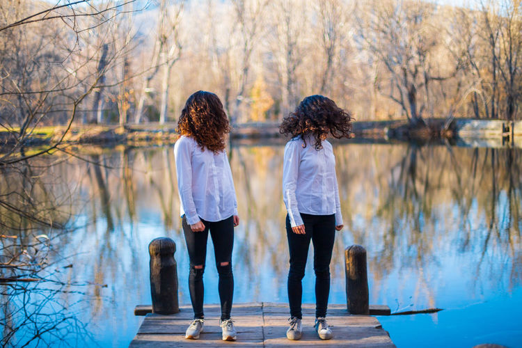 Full length of friends tossing hair while standing on pier by lake in forest