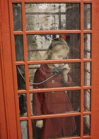 Full length of girl standing in phone booth