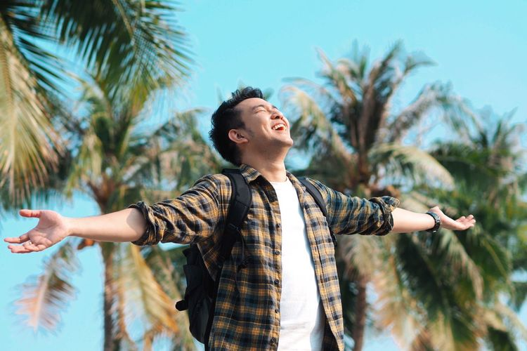 Cheerful man with arms outstretched standing against palm trees