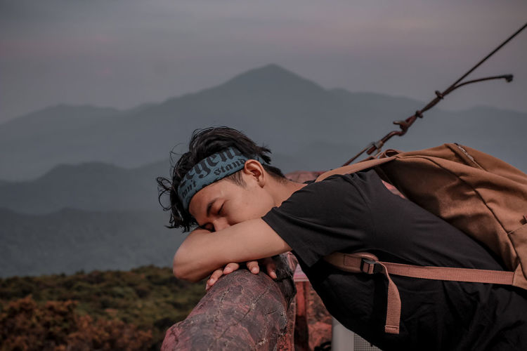 Side view of baby girl against mountain range against sky