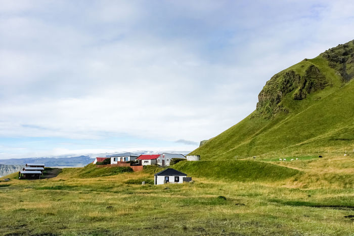 The houses in Myrdal village on Atlantic South Coast. Grass Green Houses Beauty In Nature Cloud - Sky Day Field Grass Green Color Icland Trip Land Vehicle Landscape Mode Of Transport Mosscovered Mountain Nature No People Outdoors Scenics Sky Tranquil Scene Tranquility Transportation Vik
